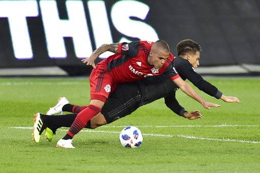 Toronto FC defender Auro, left, takes down D.C. United midfielder Yamil Asad and picks up a yellow card on the play during the first half of an MLS soccer match Wednesday, June 13, 2018, in Toronto. (Frank Gunn/The Canadian Press via AP)