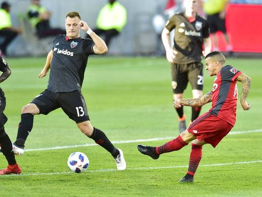 Toronto FC forward Sebastian Giovinco (10) take a shot toward the net as D.C. United's Frederic Brillant (13) defends during the first half of an MLS soccer match Wednesday, June 13, 2018, in Toronto. (Frank Gunn/The Canadian Press via AP)