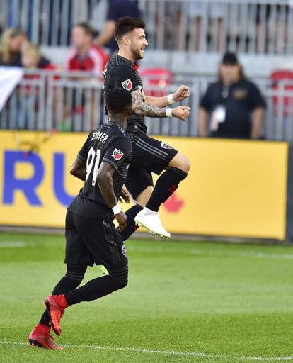 D.C. United forward Paul Arriola celebrates his goal against Toronto FC with teammate Oniel Fisher (91) during the first half of an MLS soccer match Wednesday, June 13, 2018, in Toronto. (Frank Gunn/The Canadian Press via AP)