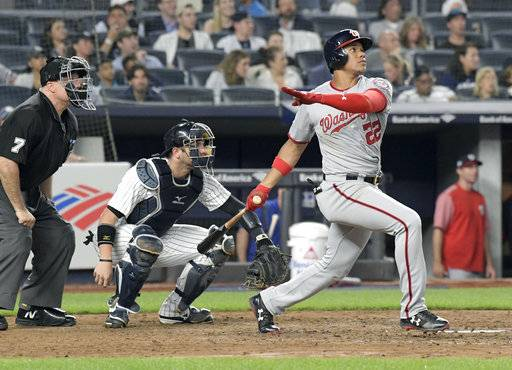 Washington Nationals' Juan Soto watches his home run in front New York Yankees catcher Austin Romine (28) and umpire Brian O'Nora uring the seventh inning of a baseball game Wednesday, June 13, 2018, at Yankee Stadium in New York.