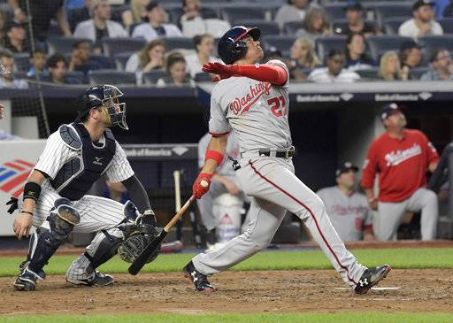 Washington Nationals' Juan Soto watches his three-run home run in front of New York Yankees catcher Austin Romine during the fourth inning of a baseball game Wednesday, June 13, 2018, at Yankee Stadium in New York.