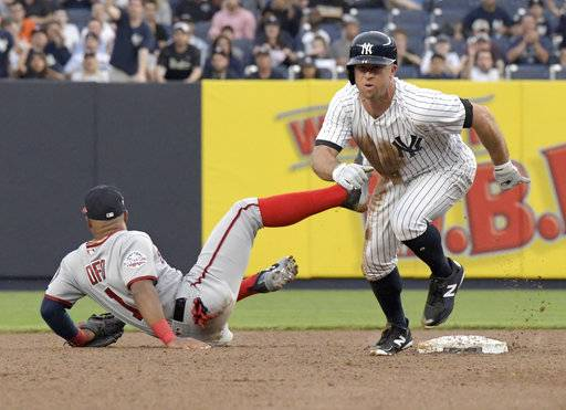 New York Yankees' Brett Gardner, right, heads to third after stealing second base as Washington Nationals shortstop Wilmer Difo (1) couldn't handle the ball thrown by catcher Spencer Kieboom for an error during the first inning of a baseball game Wednesday, June 13, 2018, at Yankee Stadium in New York.