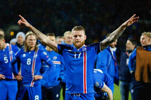 FILE - In this Monday Oct. 9, 2017 filer, Iceland's captain Aron Gunnarsson celebrates at the end of the World Cup Group I qualifying soccer match between Iceland and Kosovo in Reykjavik, Iceland. Icelandic footballers are the tallest at the World Cup in Russia, with an average height of 1.85 meters (just over 6 feet), making them especially strong in aerial duels in defense and attack.