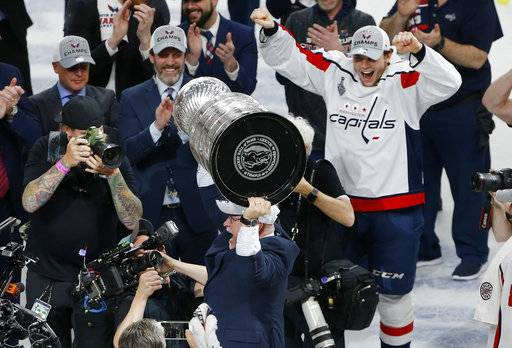 Washington Capitals head coach Barry Trotz holds up the Stanley Cup after the Capitals defeated the Vegas Golden Knights in Game 5 of the NHL hockey Stanley Cup Finals Thursday, June 7, 2018, in Las Vegas.
