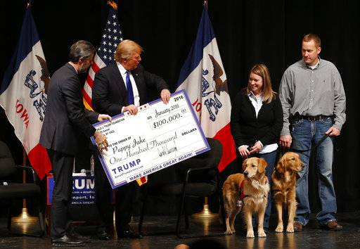 FILE - In this Jan. 30, 2016 file photo, Donald Trump, second from left, stages a check presentation with an enlarged copy of a $100,000 contribution from the Donald J. Trump Foundation to Puppy Jake, a veteran's charity, at a campaign event in Davenport, Iowa during Trump's run for president. New York Attorney General Barbara Underwood filed a lawsuit Thursday June 14, 2018, accusing Trump of illegally using his charitable foundation to pay legal settlements related to his golf clubs and to bolster his presidential campaign with Foundation disbursements such as this one in Iowa.