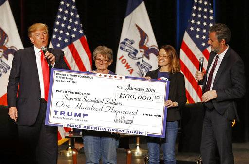FILE - In this Jan. 31, 2016 file photo, Donald Trump, left, stages a check presentation with an enlarged copy of a $100,000 contribution from the Donald J. Trump Foundation to Support Siouxland Soldiers during a campaign event in Sioux City, Iowa., during Trump's run for president. New York Attorney General Barbara Underwood filed a lawsuit Thursday June 14, 2018, accusing Trump of illegally using his charitable foundation to pay legal settlements related to his golf clubs and to bolster his presidential campaign with Foundation disbursements such as this one in Iowa. Also pictured is Jerry Falwell, Jr., right, president of Liberty University.
