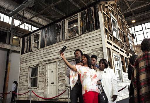 FILE - In this April 1, 2018 file photo, Cheryl Galloway, of Providence, R.I., uses a mobile phone to take a photo with family members in front of the rebuilt house of Rosa Parks at the WaterFire Arts Center in Providence, R.I. The house where Parks sought refuge in Detroit after fleeing the South will be auctioned after being turned into a work of art. Guernsey's auction house says the sale will be held mid-summer and that it's expected to fetch seven figures.