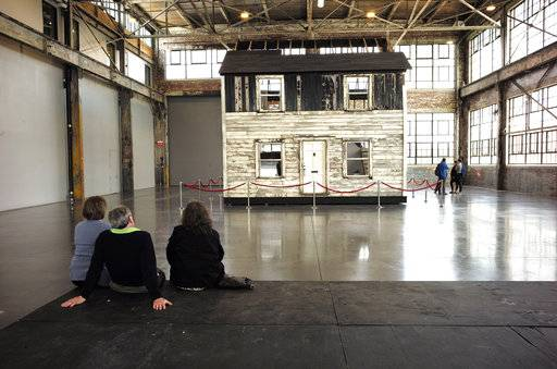 FILE - In this April 1, 2018 file photo, visitors view the rebuilt house of Rosa Parks at the WaterFire Arts Center in Providence, R.I. The house where Parks sought refuge in Detroit after fleeing the South will be auctioned after being turned into a work of art. Guernsey's auction house says the sale will be held mid-summer and that it's expected to fetch seven figures.