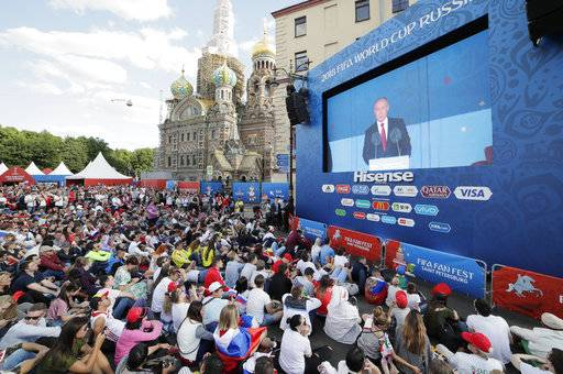 People watch a speech of Russian President Vladimir Putin on a huge screen prior the 2018 soccer World Cup match between Russia and Saudi Arabia at a fan zone in St.Petersburg, Russia, Thursday, June 14, 2018.