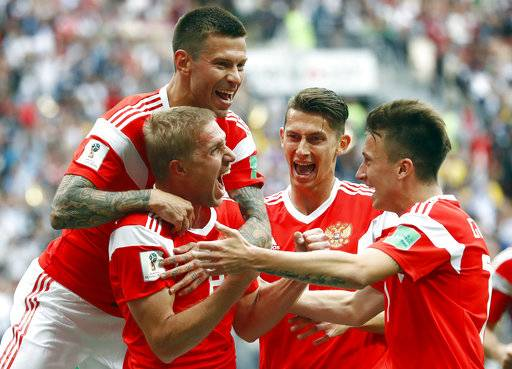 Russia's Yuri Gazinsky, left, celebrates with teammates after scoring his side's first goal during the group A match between Russia and Saudi Arabia which opens the 2018 soccer World Cup at the Luzhniki stadium in Moscow, Russia, Thursday, June 14, 2018.