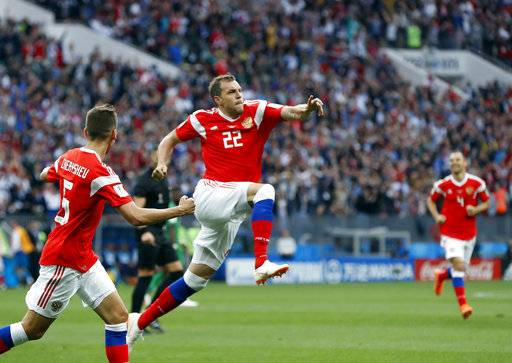 Russia's Artyom Dzyuba, center, celebrates after scoring his side's third goal during the group A match between Russia and Saudi Arabia which opens the 2018 soccer World Cup at the Luzhniki stadium in Moscow, Russia, Thursday, June 14, 2018.