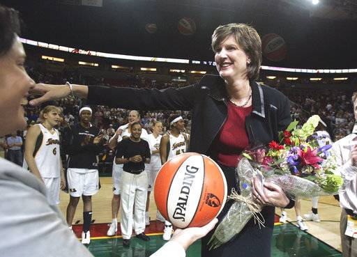 FILE - In this Aug. 19, 2005, file photo, Seattle Storm coach Anne Donovan, right, smiles as she is handed the game ball by team official Karen Bryant following the Storm's victory over the Minnesota Lyn  in Seattle. The victory gave Donovan her 100th career WNBA victory as a coach, the first woman to reach that plateau. Donovan died Wednesday, June 13, 2018, of heart failure. She was 56. Donovan's family confirmed the death in a statement.