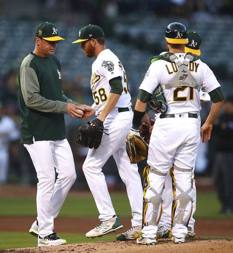 Oakland Athletics pitcher Paul Blackburn (58) hands the ball to manager Bob Melvin as he is removed during the second inning of the team's baseball game against the against the Houston Astros on Wednesday, June 13, 2018, in Oakland, Calif.