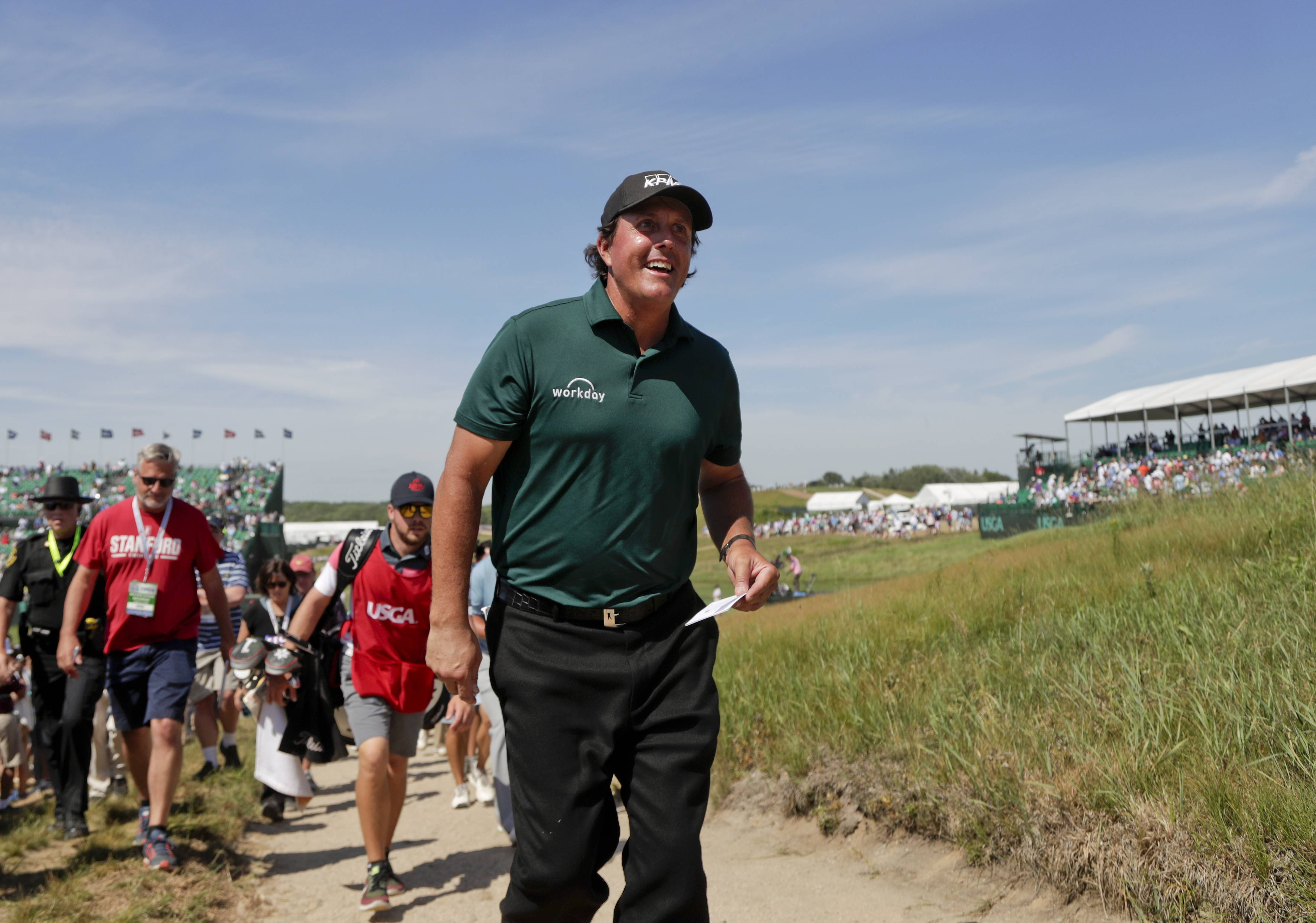 Phil Mickelson walks off the course Saturday after finishing the 18th hole during the third round of the U.S. Open Golf Championship in Southampton, N.Y.