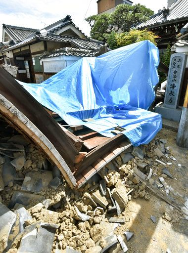 The gate of Jokyoji temple collapses after an earthquake in Ibaraki city, Osaka, western Japan, Monday, June 18, 2018. A strong earthquake knocked over walls and set off scattered fires around metropolitan Osaka on Monday morning. (Keiji Uesho/Kyodo News via AP)