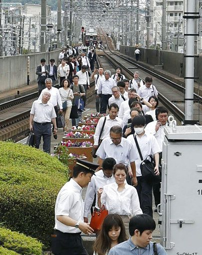 Passengers walk on railroad as train service was suspended following an earthquake in Ikeda, Osaka, Monday, June 18, 2018. A strong earthquake shook the city of Osaka in western Japan on Monday morning, causing scattered damage including broken glass and partial building collapses. (Takaki Yajima/Kyodo News via AP)
