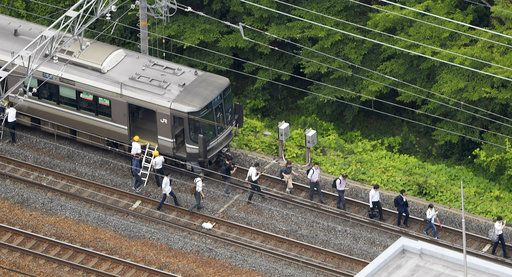 Passengers walk on railroad as the train service was suspended following an earthquake in Takatsuki, Osaka, Monday, June 18, 2018.  A strong earthquake shook the city of Osaka in western Japan on Monday morning, causing scattered damage including broken glass and partial building collapses. (Yohei/Nishimura/Kyodo News via AP)