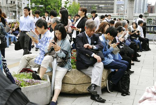 People wait for train service to resume following an earthquake in Osaka, Monday, June 16, 2018. A strong earthquake shook the city of Osaka in western Japan on Monday morning, causing scattered damage including broken glass and partial building collapses. (Junko Ozaki/Kyodo News via AP)