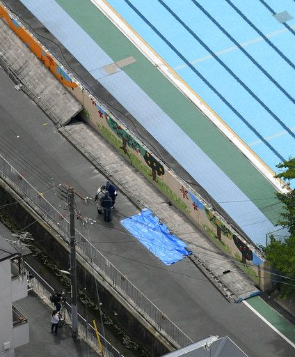 Police inspect the site, covered by blue sheet, where a girl was killed by fallen wall, following an earthquake near an elementary school in Takatsuki, Osaka, Monday, June 18, 2018. A strong earthquake knocked over walls and set off scattered fires around the city of Osaka in western Japan on Monday morning.(Yohei Nishimura/Kyodo News via AP)