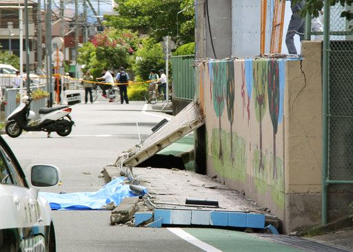 Wall lies on road after it fell down following an earthquake near an elementary school in Takatsuki, Osaka, Monday, June 18, 2018. A strong earthquake knocked over walls and set off scattered fires around the city of Osaka in western Japan on Monday morning.(Shuichiro Sugiyama/Kyodo News via AP)