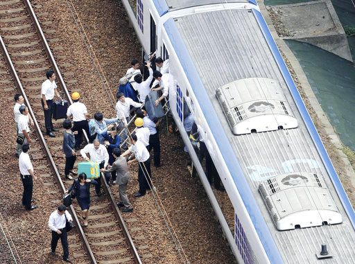 Passengers descend from a train on the track after train service was suspended to check for damage following an earthquake in Takatsuki city, Osaka, western Japan, Monday, June 18, 2018. A strong earthquake knocked over walls and set off scattered fires around metropolitan Osaka on Monday morning. (Kyodo News via AP)