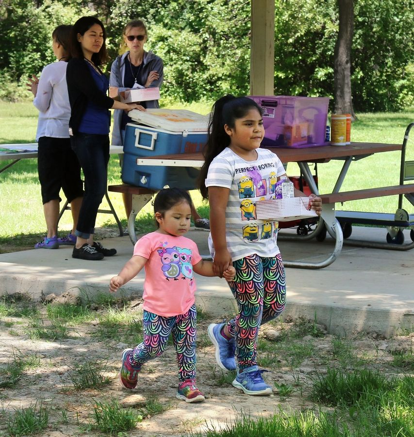 Dulce Garcia, 7, walks with her sister, Jimena, 2, after receiving free lunches during the first day of a free summer meals program offered last year by a charitable group at Gordon Ray Park in Mundelein.