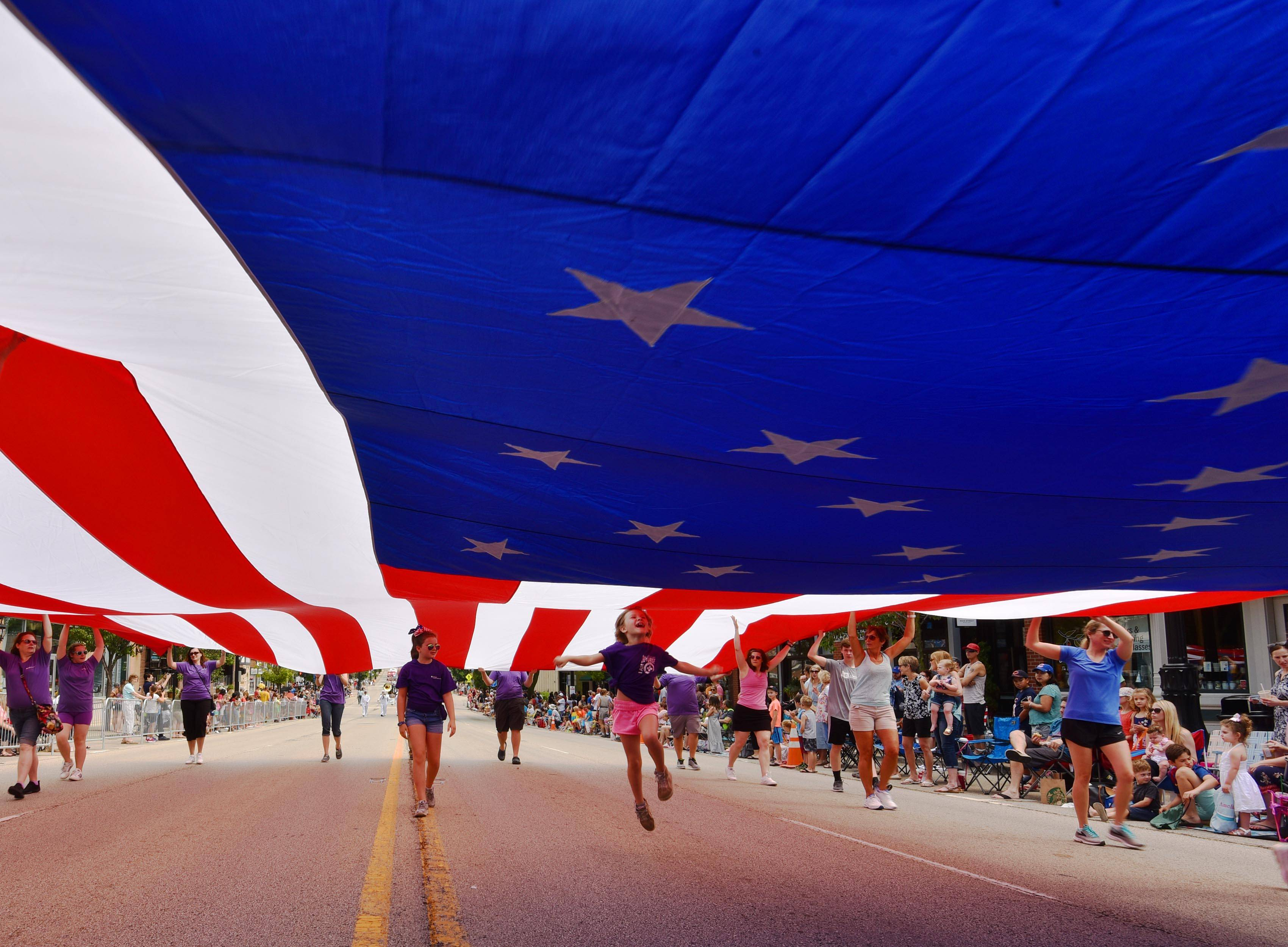 A young girl jumps with joy under a huge American Flag being carried by Advocate Condell Medical Center personnel at the start of the Libertyville Days Parade on Saturday in downtown Libertyville.