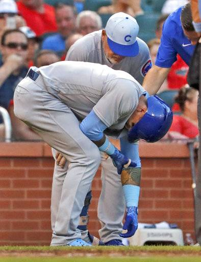 Chicago Cubs' Javier Baez, front, doubles over as he is checked on by manager Joe Maddon after being hit by a pitch during the third inning of a baseball game against the St. Louis Cardinals Sunday, June 17, 2018, in St. Louis. Baez left the game.