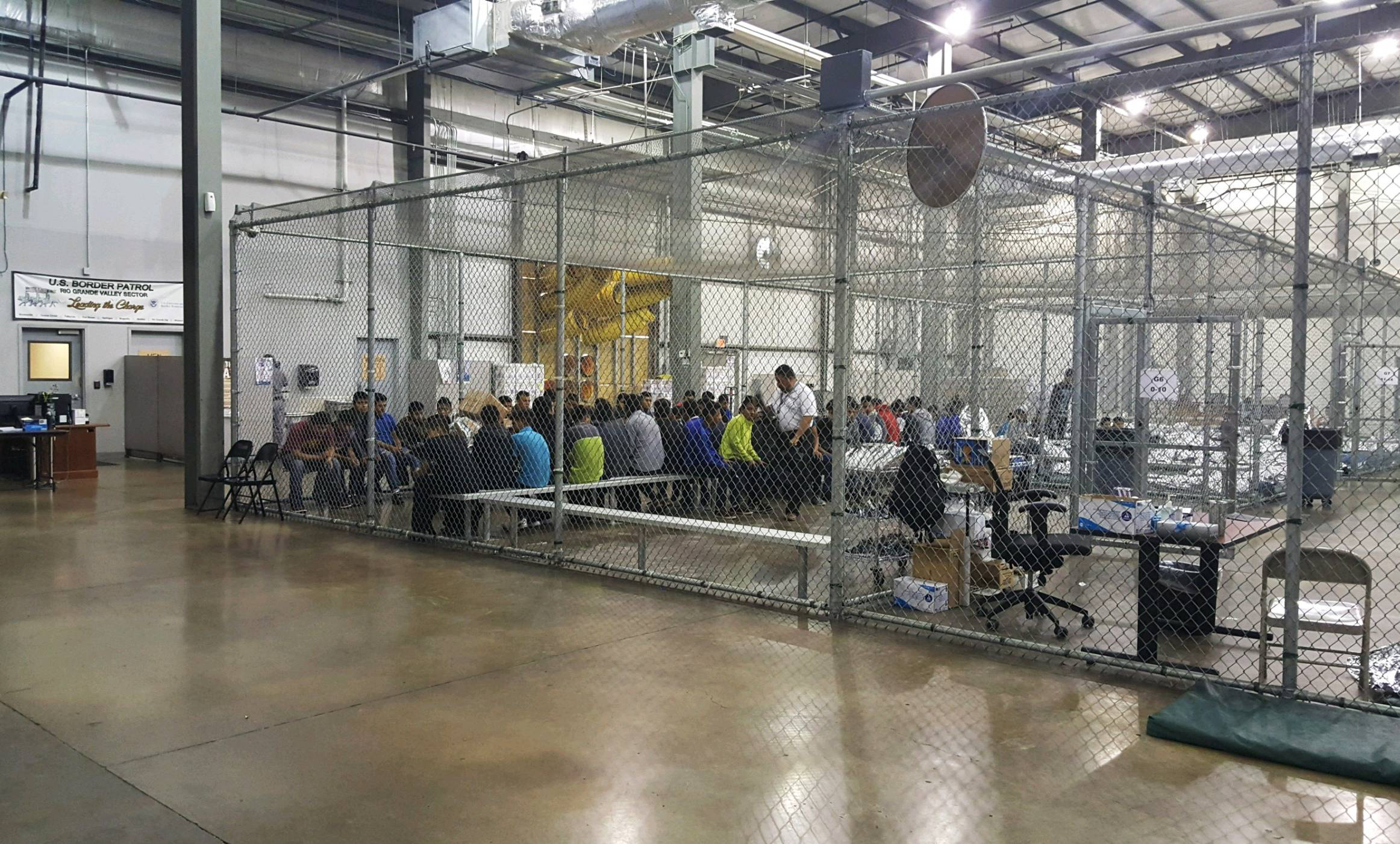 In this photo provided by U.S. Customs and Border Protection, people who've been taken into custody related to cases of illegal entry into the United States sit Sunday in one of the cages at a facility in McAllen, Texas.