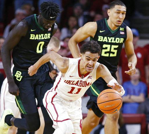FILE - In this Jan. 30, 2018, file photo, Oklahoma guard Trae Young (11) heads up the court with a steal in front of Baylor forwards Jo Lual-Acuil Jr. (0) and Tristan Clark (25) during the second half of an NCAA college basketball game in Norman, Okla. Young is a possible pick in Thursday's NBA Draft.