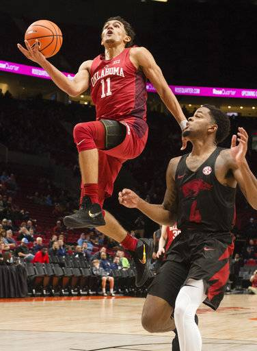 FILE - In this Nov. 23, 2017, file photo, Oklahoma guard Trae Young, left, scores a basket as he is guarded by Arkansas guard Daryl Macon, right, during the first half in an NCAA college basketball game at the Phil Knight Invitational Tournament in Portland, Ore. Young is a possible pick in Thursday's NBA Draft.