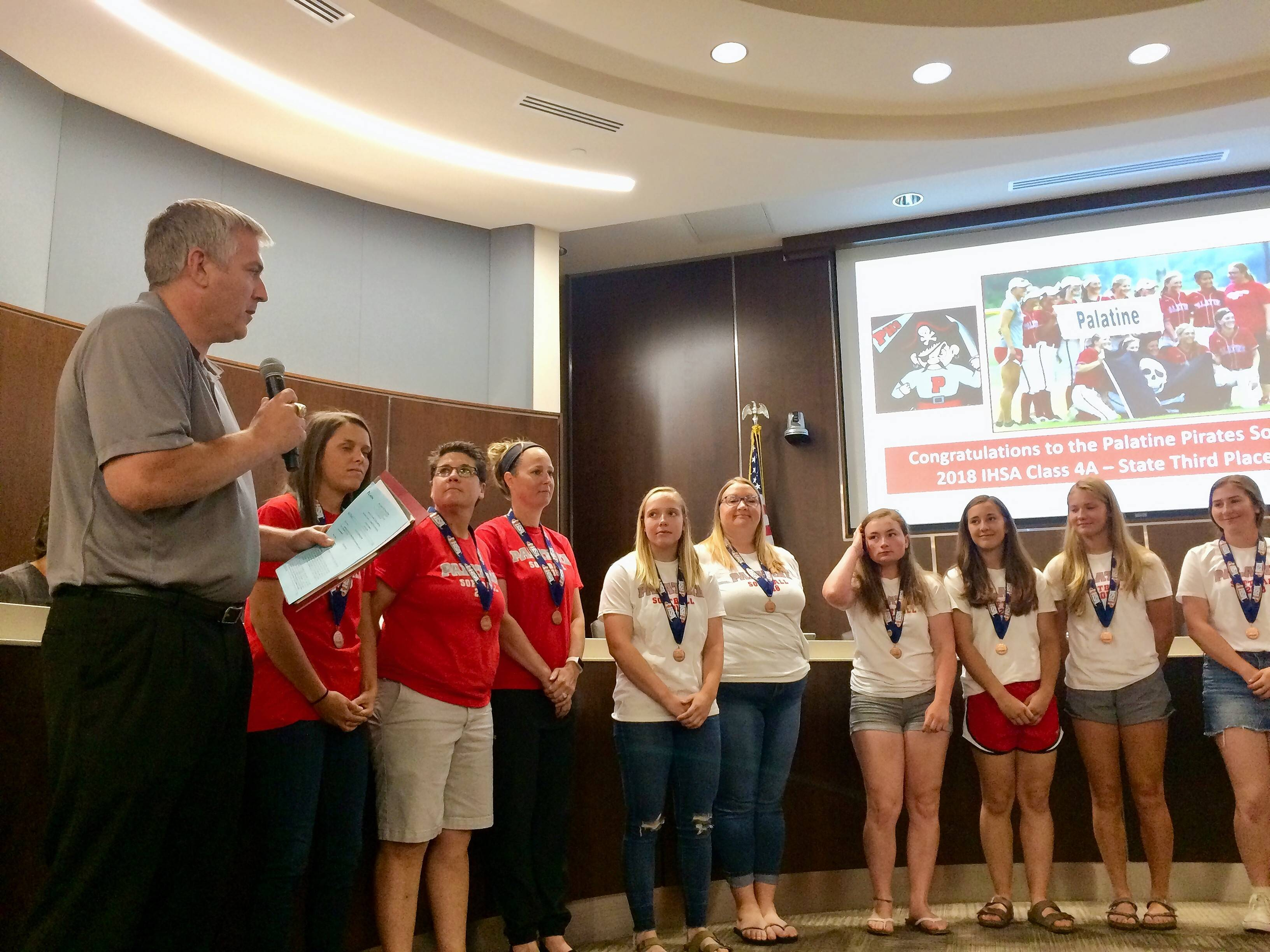 Palatine High School's girls softball team was honored at this week's village council meeting for placing third in the Class 4A state tournament. Palatine Mayor Jim Schwantz, far left, addressed the team about its achievement.
