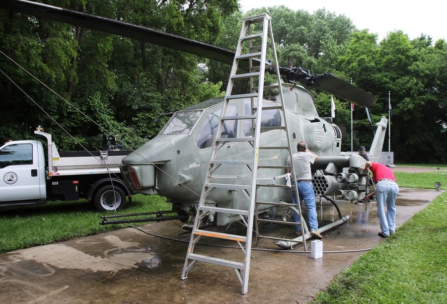 Volunteers sand and scrape the old paint on a AH-1 Cobra helicopter Wednesday at Veterans Memorial Park in Island Lake.