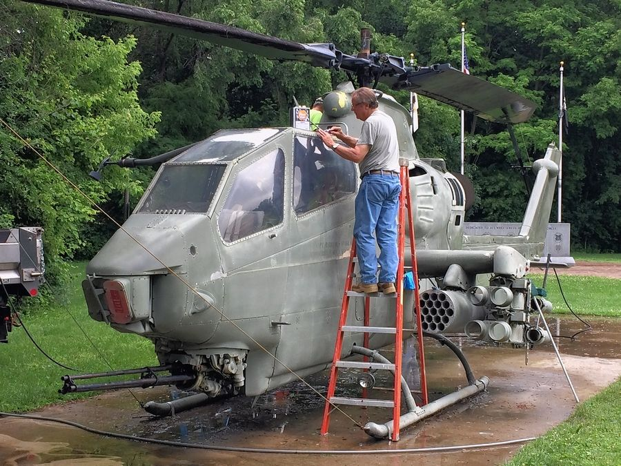 Volunteer Chet Malanowski scrapes loose paint off the Cobra helicopter at Veterans Memorial Park in Island Lake. Volunteers are going to paint the helicopter next month.