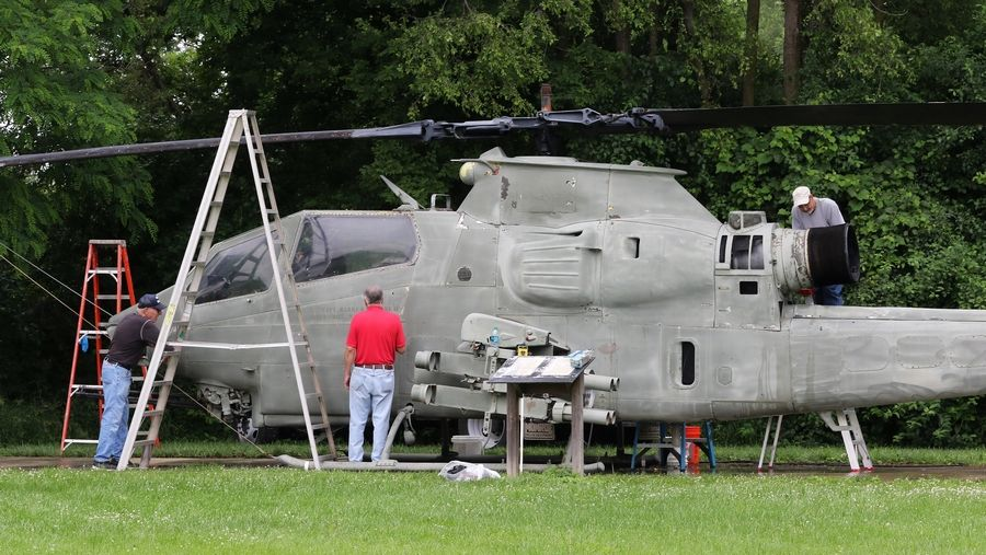 Volunteers sand and scrape the old paint on an AH-1 Cobra helicopter Wednesday at Veterans Memorial Park in Island Lake. The helicopter will get a new coat of paint later this summer.