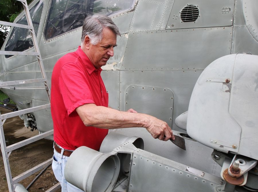 Island Lake Mayor Charles Amrich scrapes the exterior of an AH-1 Cobra helicopter Wednesday at Veterans Memorial Park in Island Lake.