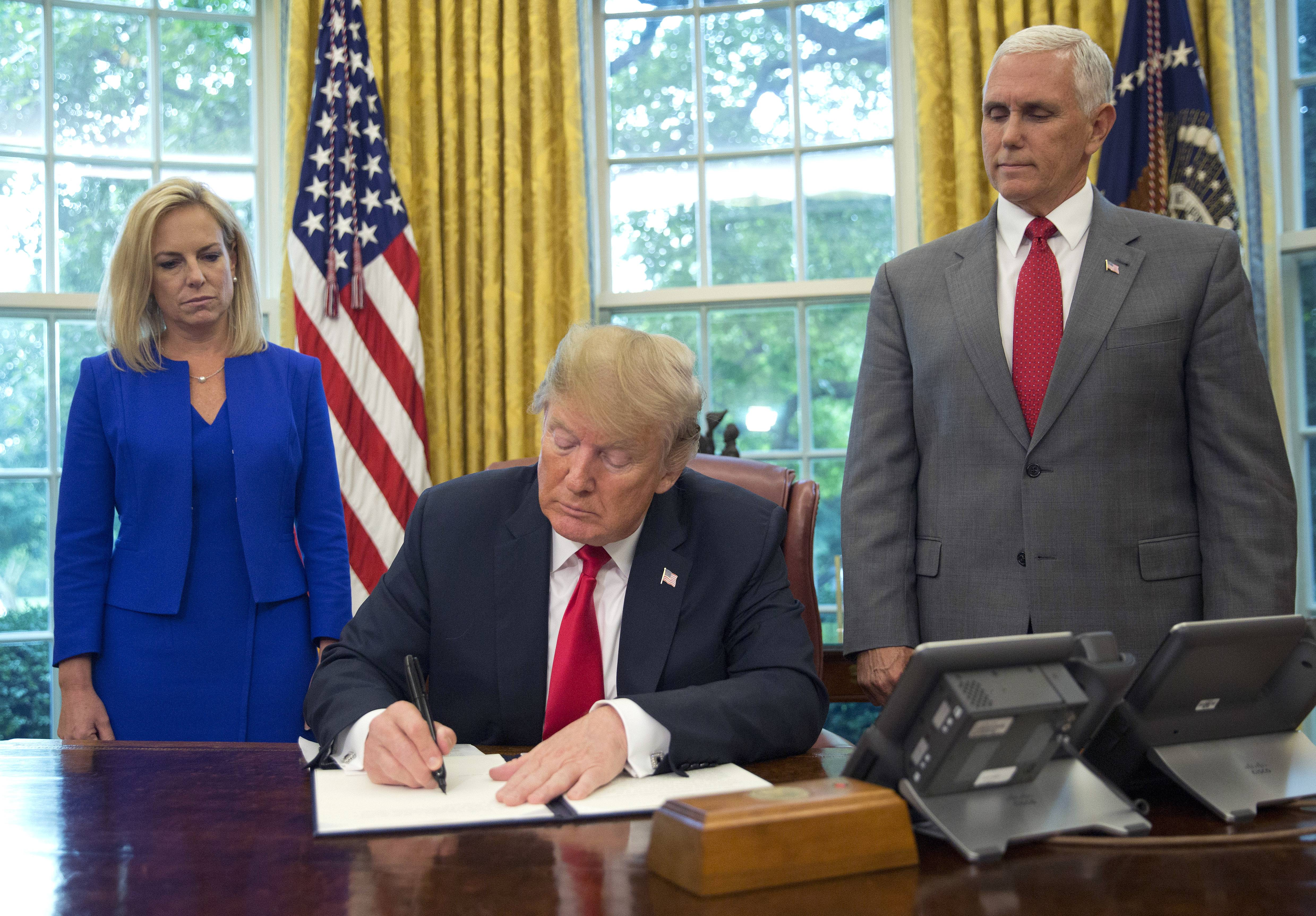President Donald Trump signs an executive order Wednesday to keep families together at the border, but says that the 'zero-tolerance' prosecution policy will continue, during an event in the Oval Office of the White House in Washington. Standing behind Trump are Homeland Security Secretary Kirstjen Nielsen, left, and Vice President Mike Pence.