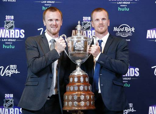 Daniel Sedin, right, and Henrik Sedin pose with the King Clancy Memorial Trophy after winning the award at the NHL Awards, Wednesday, June 20, 2018, in Las Vegas.