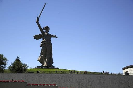 In this Sunday, June 17, 2018 photo, tourists visit the Motherland Calls monument which commemorates the victims of the Battle of Stalingrad, in which the Red Army turned back Nazi Germany's army in Volgograd, Russia. Nearly 60 years since it changed its name to Volgograd, the Russian city once called Stalingrad and its bloody history loom large even in the midst of the fun and football of the World Cup.