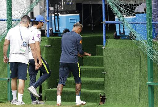 Brazil's Neymar, right, leaves a training session because of pain in his right ankle, in Sochi, Russia, Tuesday, June 19, 2018. Brazil will face Costa Rica on June 22 in the group E for the soccer World Cup.