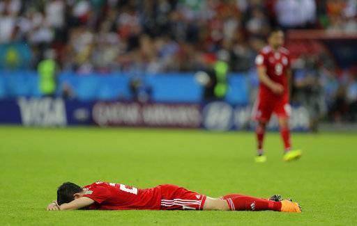 Iran's Sardar Azmoun lies flat out in the ground after the end of the group B match between Iran and Spain at the 2018 soccer World Cup in the Kazan Arena in Kazan, Russia, Wednesday, June 20, 2018. Spain won the game 1-0.