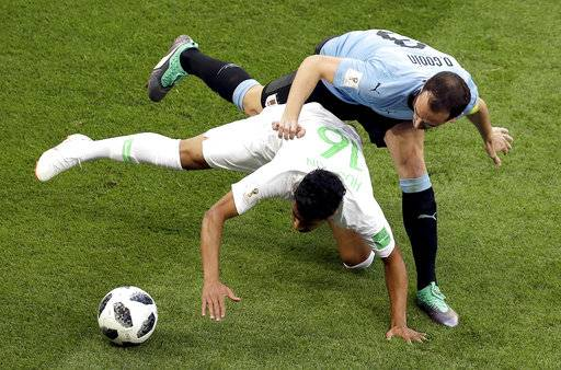 Saudi Arabia's Hussain Almoqahwi , bottom and Uruguay's Diego Godin, top, challenge for the ball during the group A match between Uruguay and Saudi Arabia at the 2018 soccer World Cup in Rostov Arena in Rostov-on-Don, Russia, Wednesday, June 20, 2018.