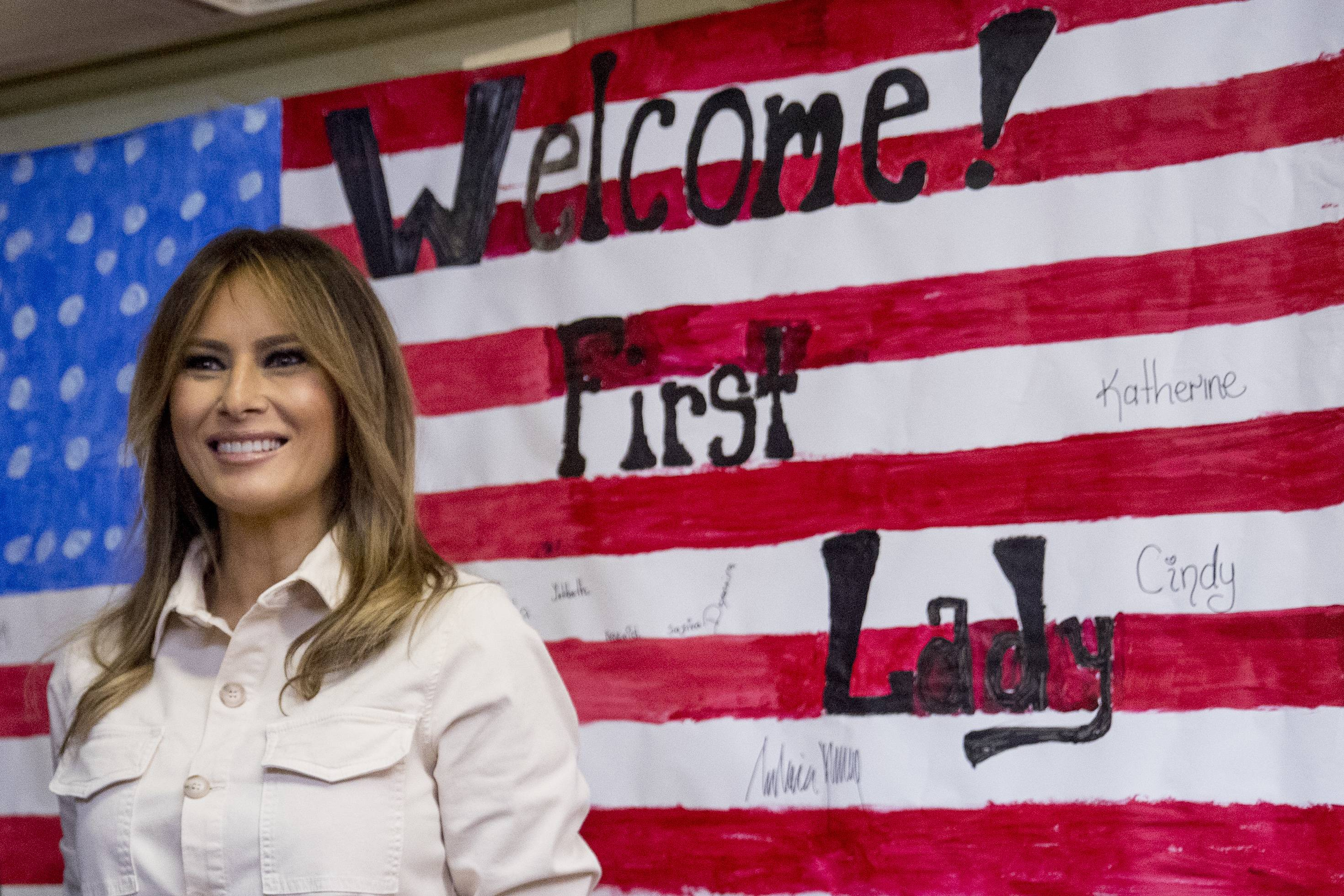 First lady Melania Trump smiles Thursday after signing American flag artwork while visiting the Upbring New Hope Children Center run by the Lutheran Social Services of the South in McAllen, Texas.