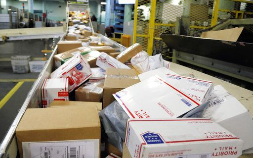 FILE- In this Dec. 14, 2017, file photo, packages travel on a conveyor belt for sorting at the main post office in Omaha, Neb. States will be able to force shoppers to pay sales tax when they make online purchases under a Supreme Court decision Thursday, June 21, 2018, that will leave shoppers with lighter wallets but is a big win for states.