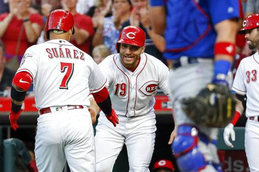 Cincinnati Reds' Eugenio Suarez (7) celebrates with Joey Votto (19) after hitting a two-run home run off Chicago Cubs starting pitcher Jose Quintana during the fifth inning of a baseball game Friday, June 22, 2018, in Cincinnati. (AP Photo/John Minchillo)