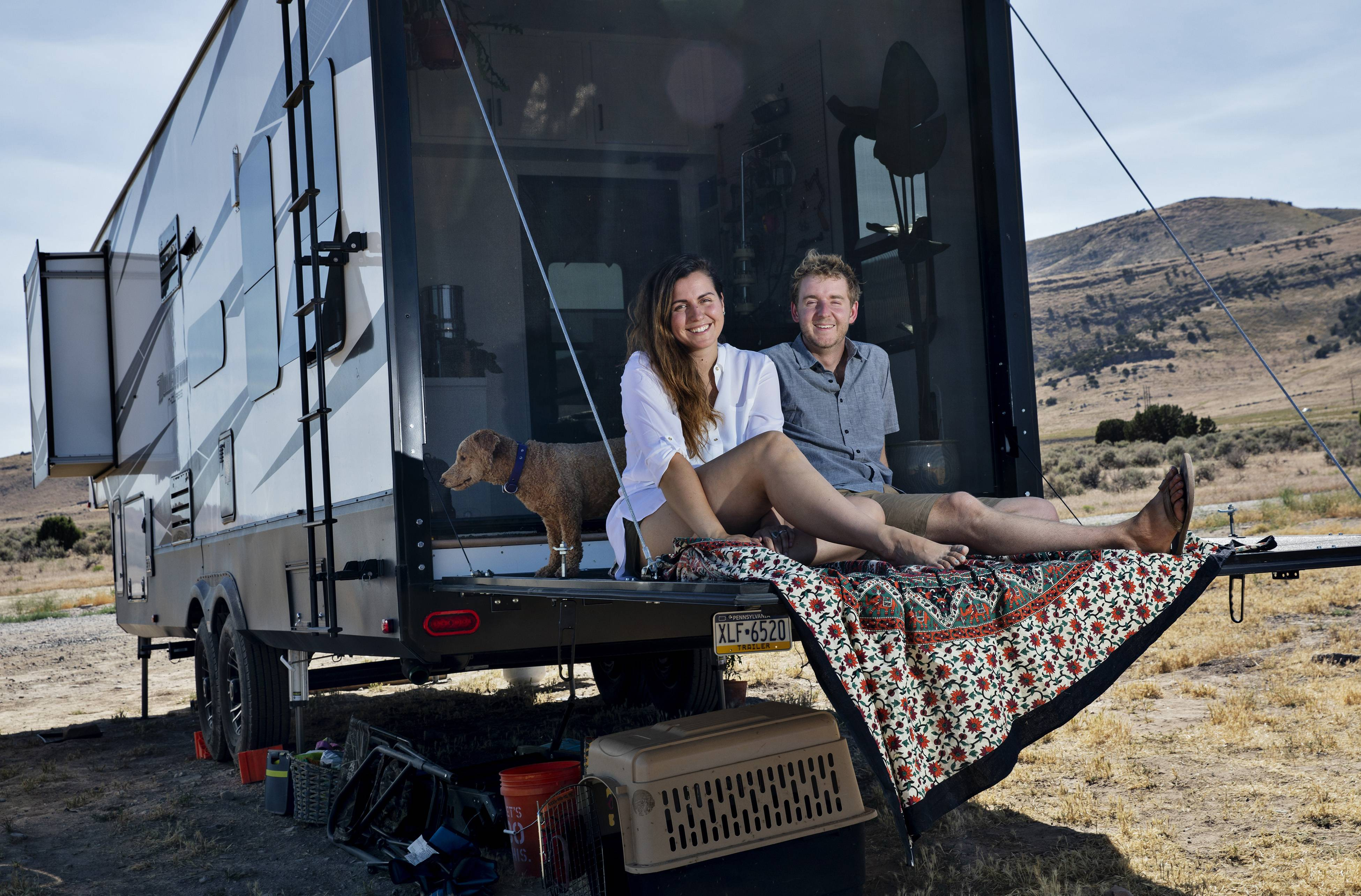 Mandy and Kevin Holesh relax with one of their two dogs at their RV. They were parked last week at Utah Lake in Saratoga Springs, Utah, far from their previous home in Pittsburgh.