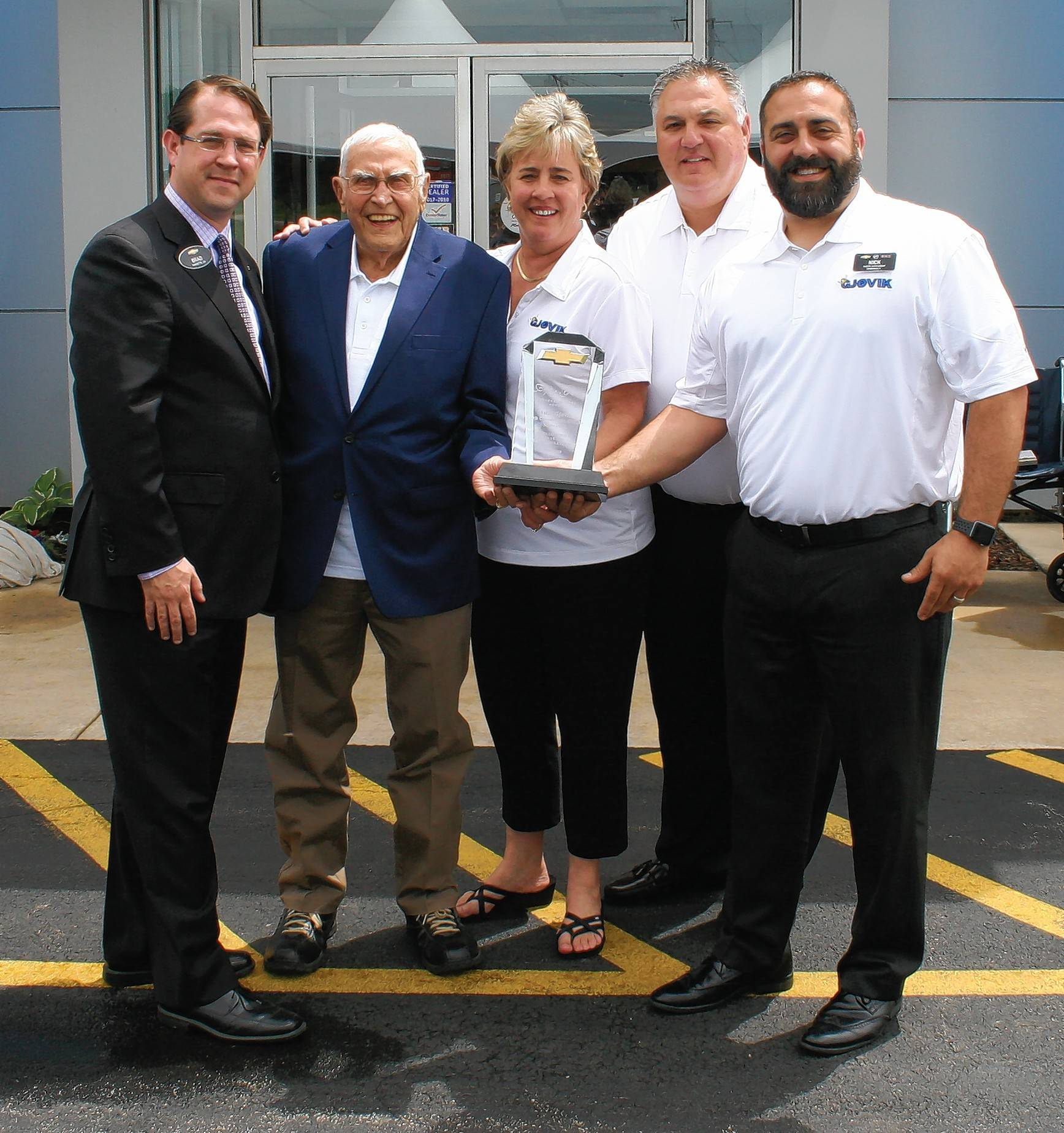 Brad Finley, Chevrolet Zone Manager, presents Olaf Gjovik with the 50 Year Award for this dealership milestone. Also pictured right of Gjovik's are employees Kris Mieszala, Fred Squillo and Nick Oeser.