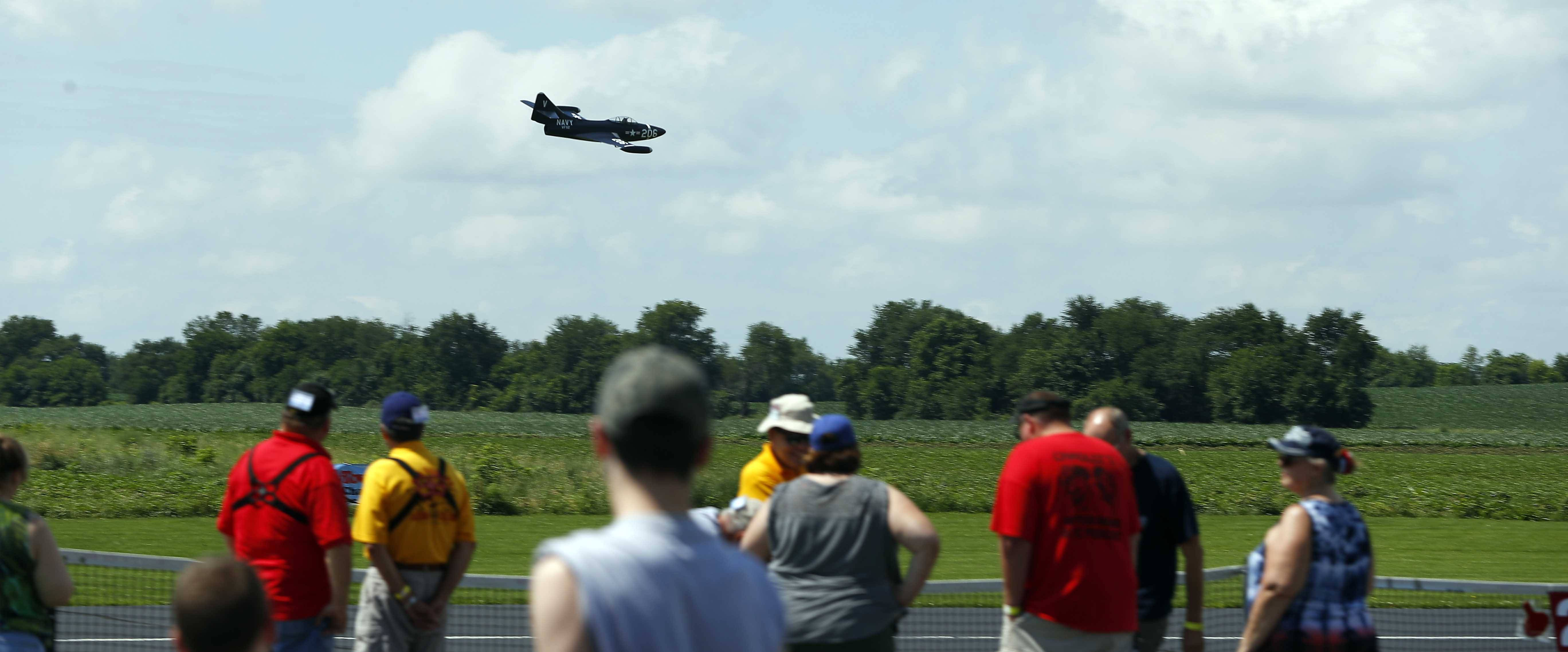 People line up to watch as a radio-controlled plane races past Saturday during the Windy City Warbirds and Classics radio-controlled model air show, sponsored by the Fox Valley Aero Club.