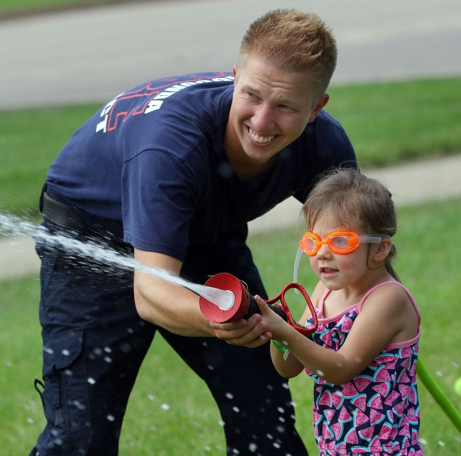 Wauconda firefighter Clint Herdegen helps 3-year-old Emma Kirtley participate in a kids water fight competition during Wauconda Fest in Cook Park Saturday.