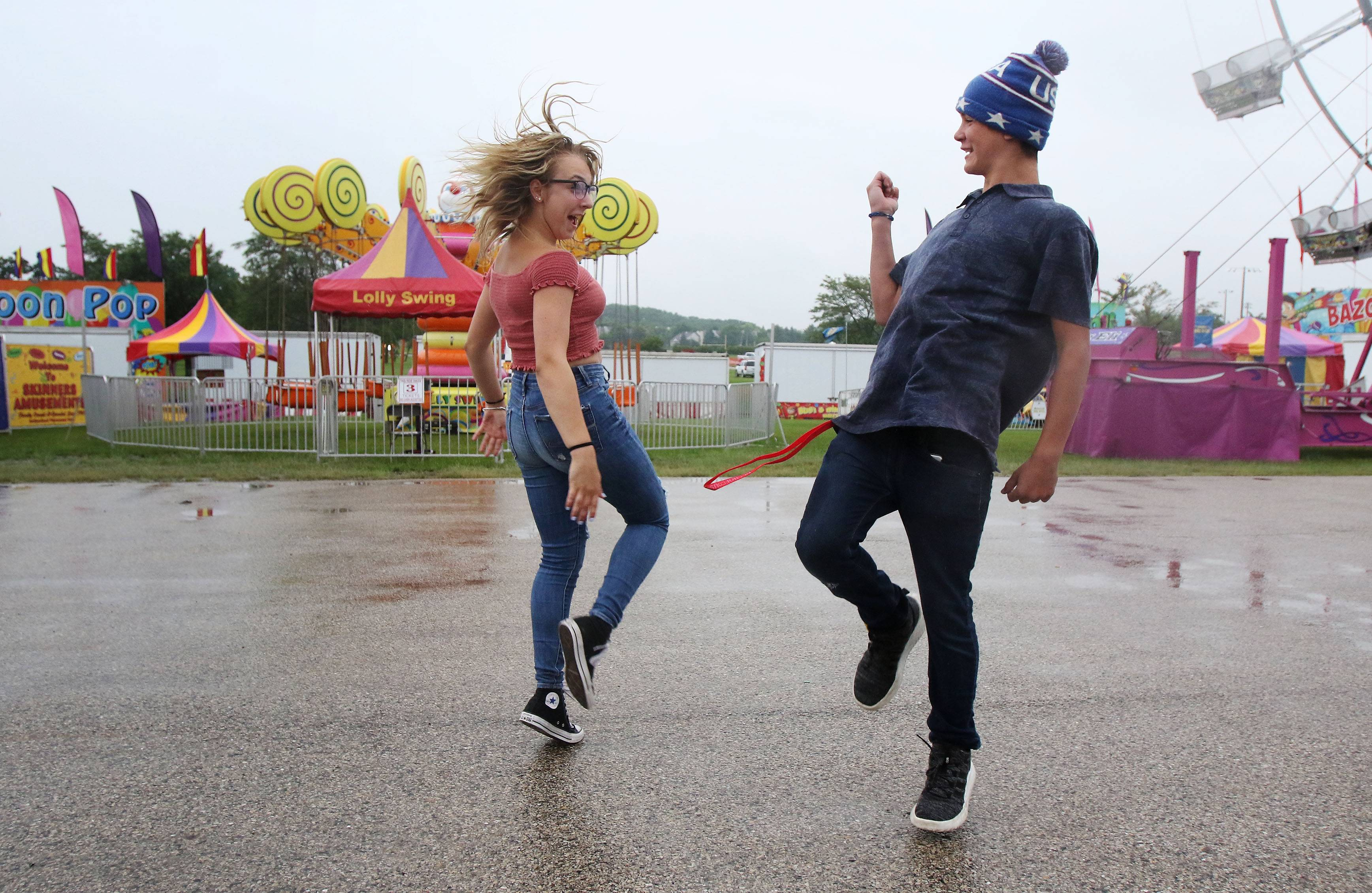 Thirteen-year-olds Nataleigh Miller and Charlie Spencer, of Wauconda dance in the rain during the first day of the Wauconda Fest at Cook Park on Thursday. Steady rain throughout the day affected attendance with carnival rides closed for the day.